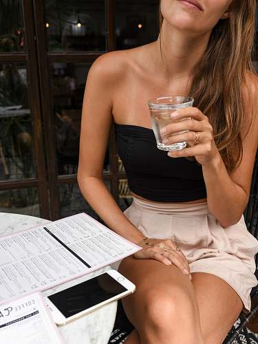 human woman in black crop top holding clear rock glass people