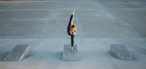 human woman in black sleeveless shirt doing yoga grey
