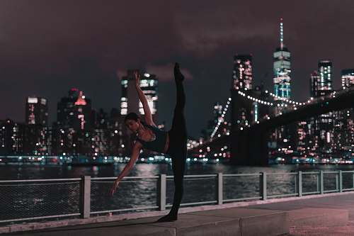 human woman in black sports bra and tights doing ballet position on sidewalk during nighttime dance