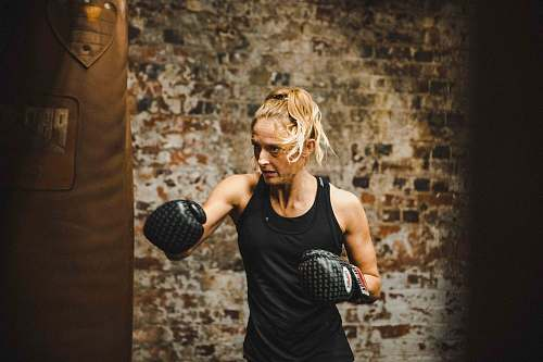 human woman in black tank top wearing boxing gloves sport