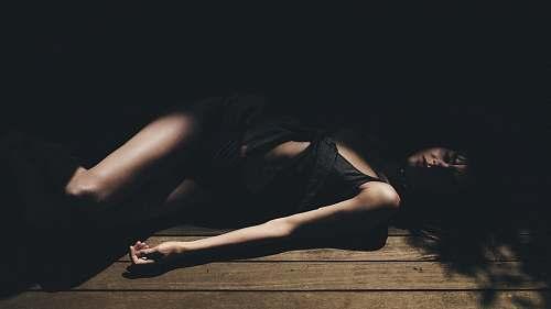 people woman lying on brown wooden floor human