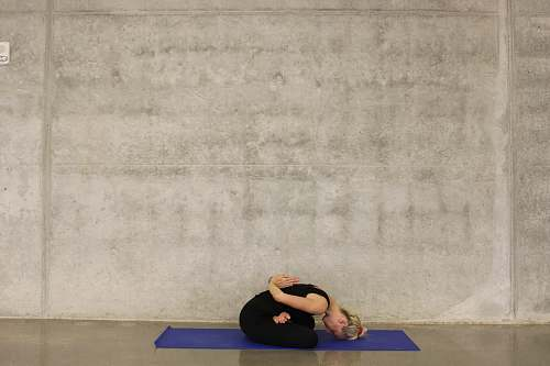 exercise woman sitting down on blue yoga mat sports