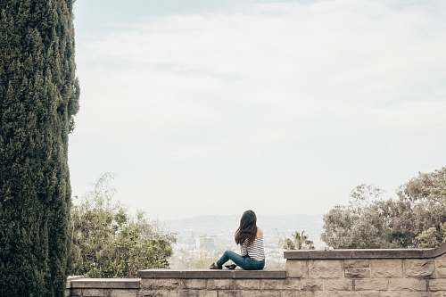 human woman sitting on concrete fence people