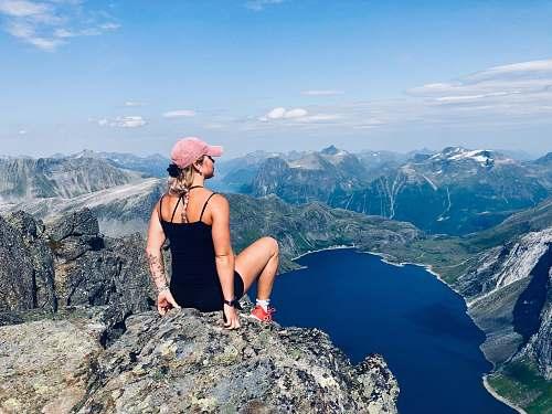 human woman sitting on mountain cliff people