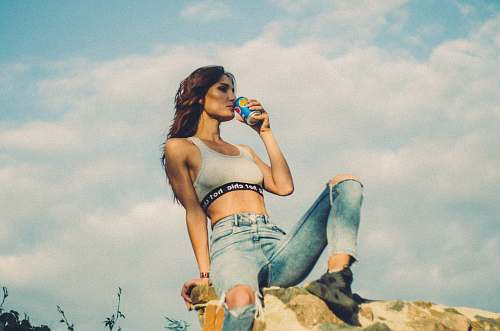human woman sitting on rocky hill drinking soda can during daytime people