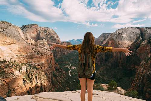 nature woman spreading her hands white standing on mountain cliff woman