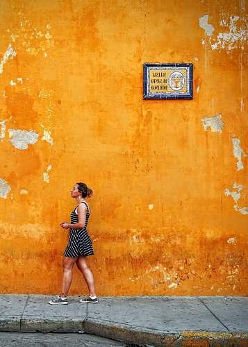 people woman walking on sidewalk yellow