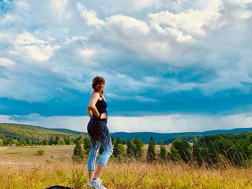 human woman wearing black and teal ju7mp suit walking on grass field apparel