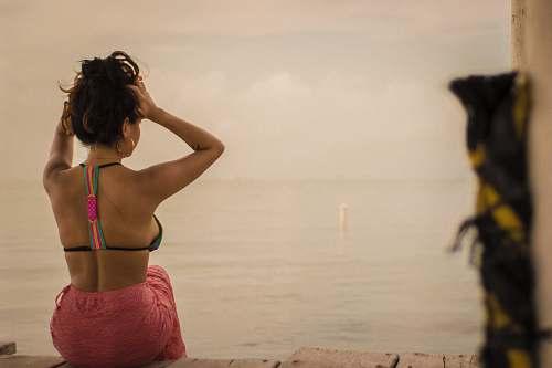 human woman wearing black halter bikini top back