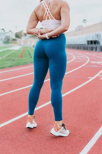 human woman wearing blue pants standing on track during daytime people