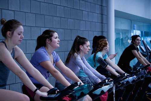 human women taking exercise on black stationary bikes in front of gray concrete wall people