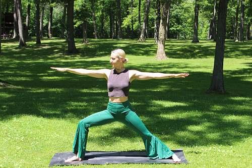 human woman doing yoga grass