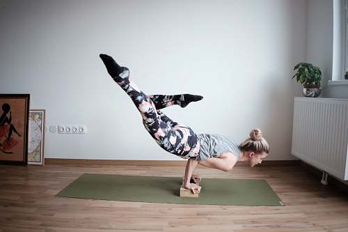 yoga woman balancing her body on olive-green mat dance pose