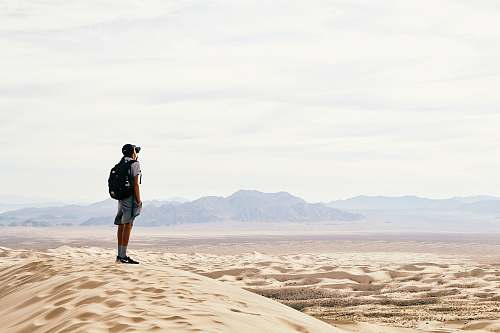 person man standing and carrying backpack in desert land desert