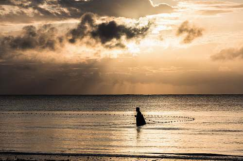 fishing person on ocean during sunrise beach