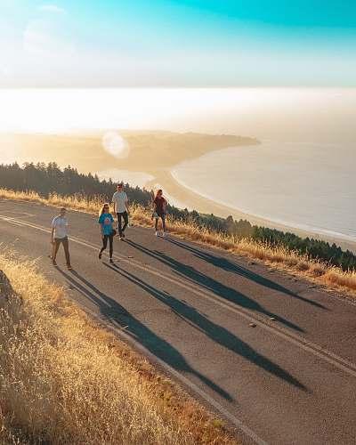 jogging four men and women walking on roadway near body of water fitness