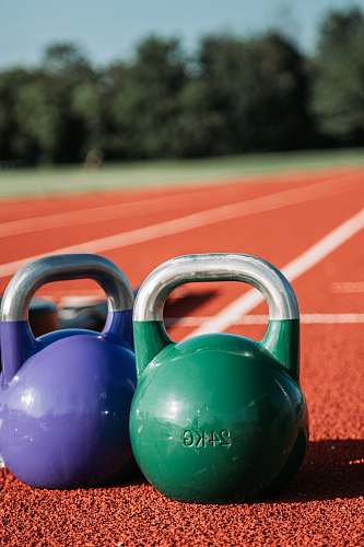 sports two green and purple kettle bells running track