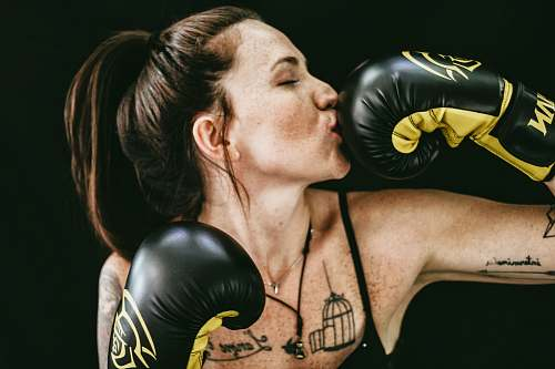fitness woman kissing black leather boxing gloves woman