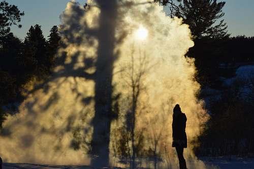 eruption person standing near trees geyser