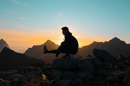sunset silhouette on man on mountain silhouette
