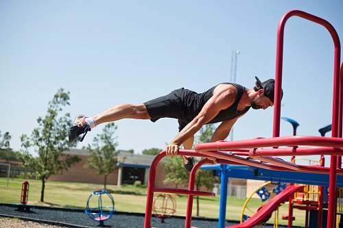 playground man doing planking on bar vehicle