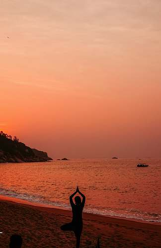 sea silhouette photo of woman doing yoga during sunset ocean