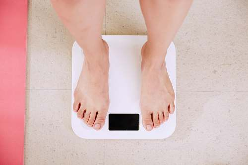 health person standing on white digital bathroom scale diet